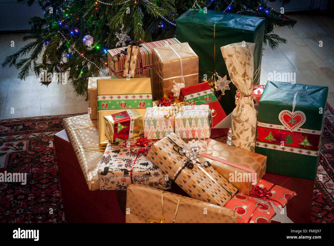 A pile of elegantly wrapped Christmas gifts. Part of a Christmas tree with lights forms the background. - Stock Image