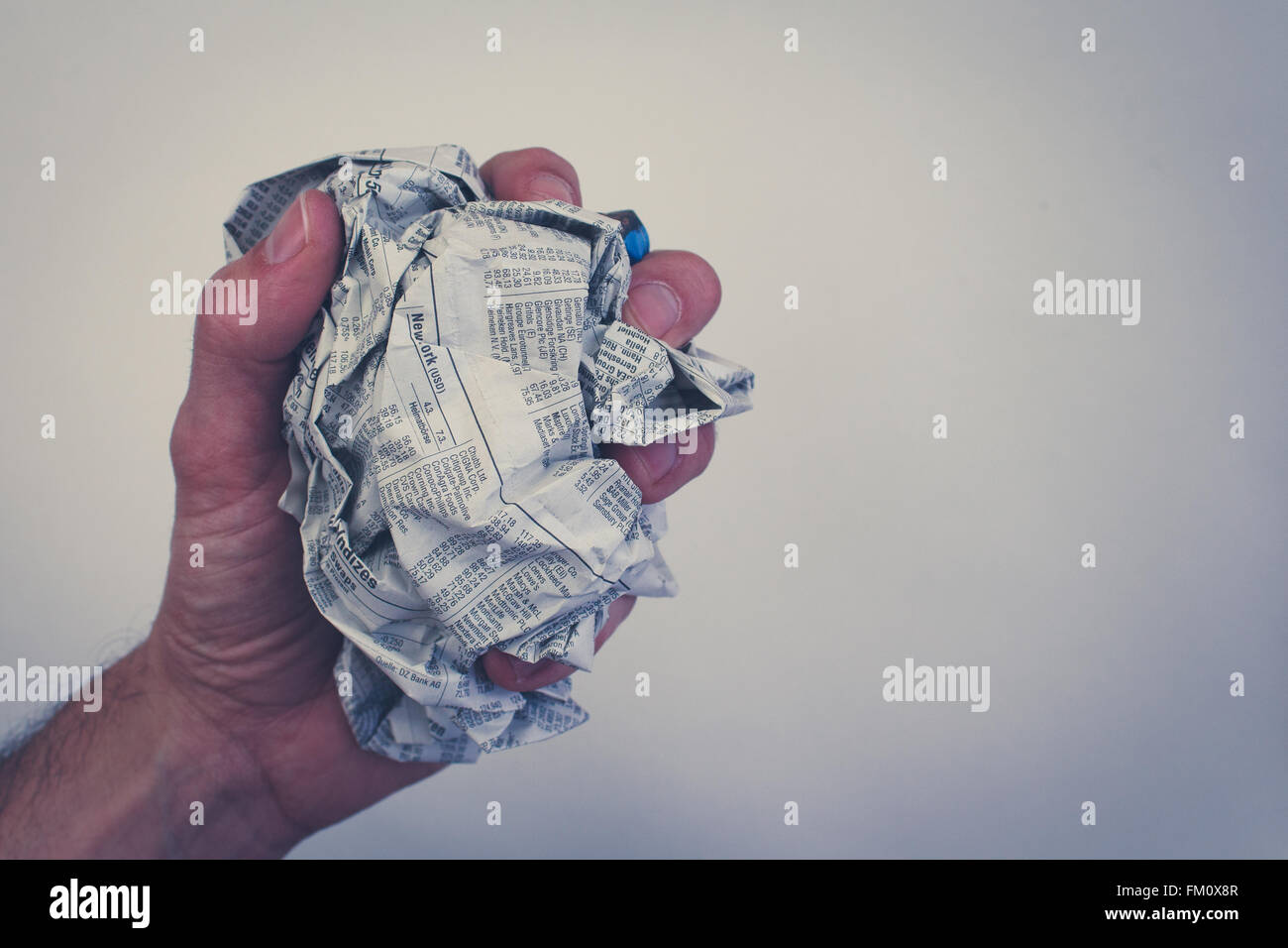 hand / fist holding screwed newspaper, german business section - Stock Image