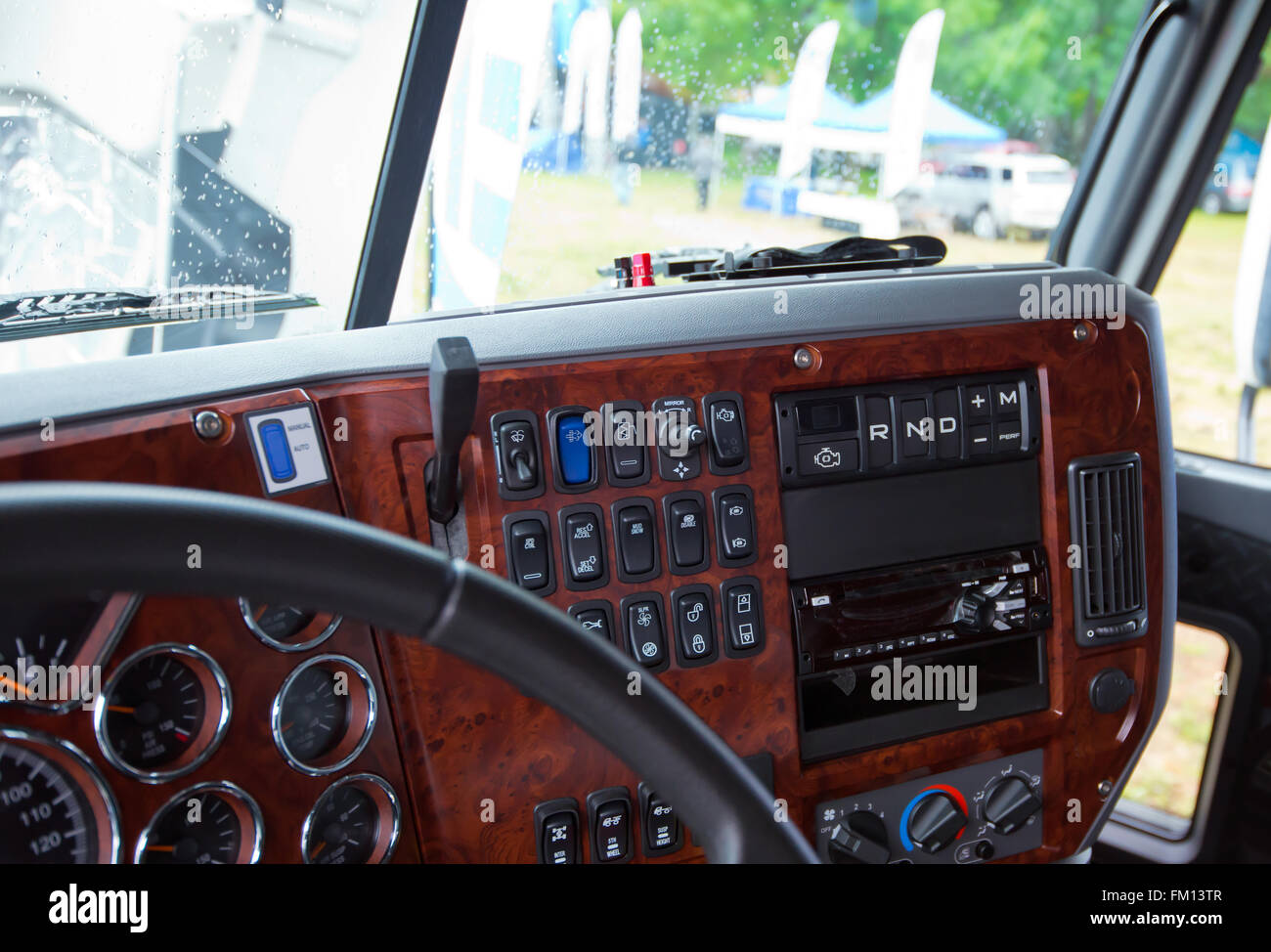 Modern ergonomic and stylish dashboard of heavy semi truck with lots of equipment, indicators, buttons, and other - Stock Image