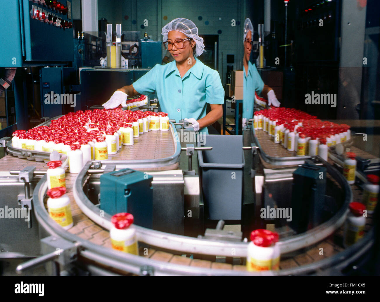 Asian factory worker performs quality control on pharmaceutical production line of Tylenol painkiller - Stock Image