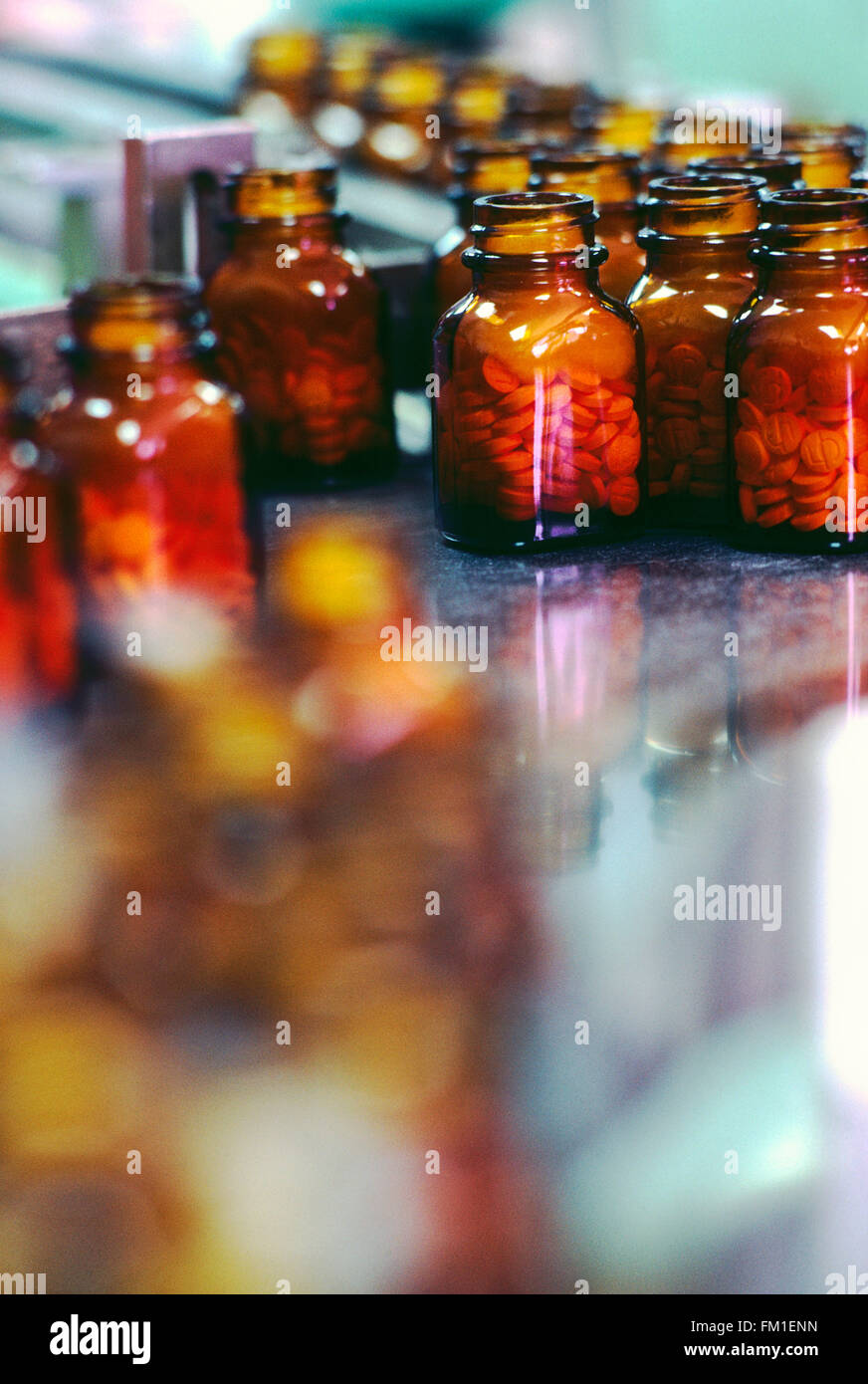 Bottled pills in manufacturing and packaging production line of pharmaceutical company - Stock Image