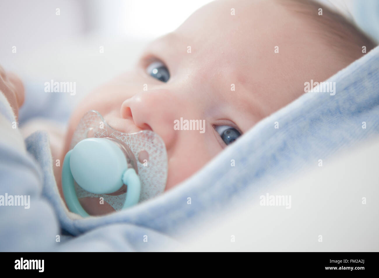 Portrait of a four months old baby with pacifier. Selective focus - Stock Image
