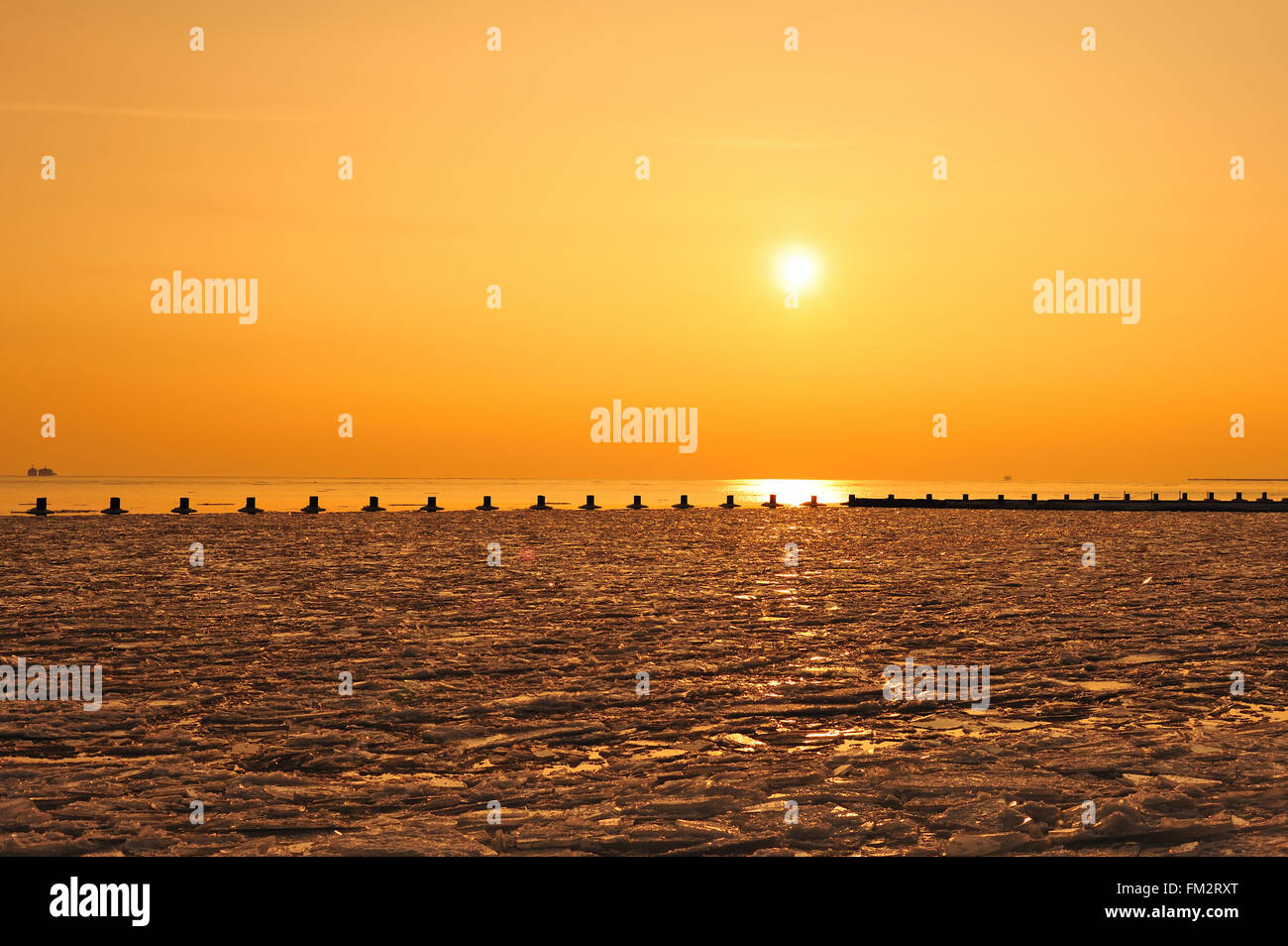 Ice clings to the waters of Lake Michigan near Fullerton Avenue Beach in Chicago as the sun rises on the city. Chicago, - Stock Image