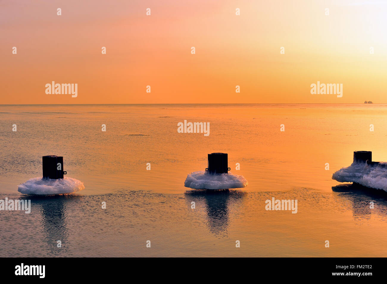 Chicago, Illinois, USA. Ice clings to breakwater pilings in Lake Michigan near Fullerton Avenue Beach as the sunrise - Stock Image