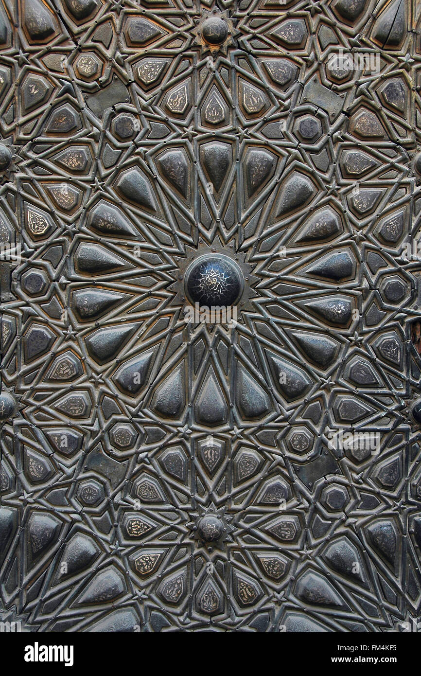 Arabesque ornament carving detail of the bronze gates at Sultan al-Mu'ayyad mosque built in 1421 by the Mamluk - Stock Image