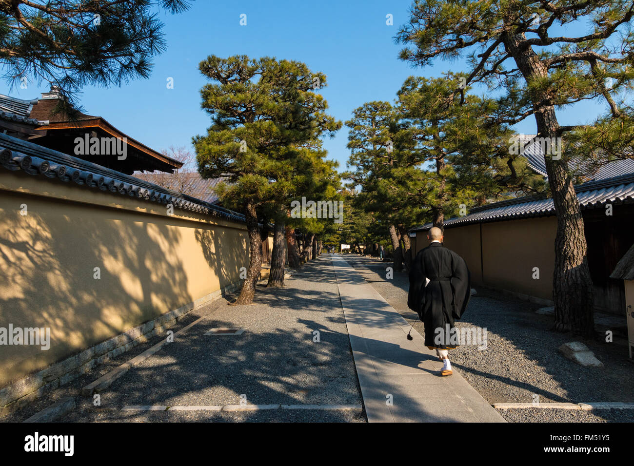 A monk walking down a path between walls in the Daitoku-ji zen buddhist temple in Kyoto - Stock Image