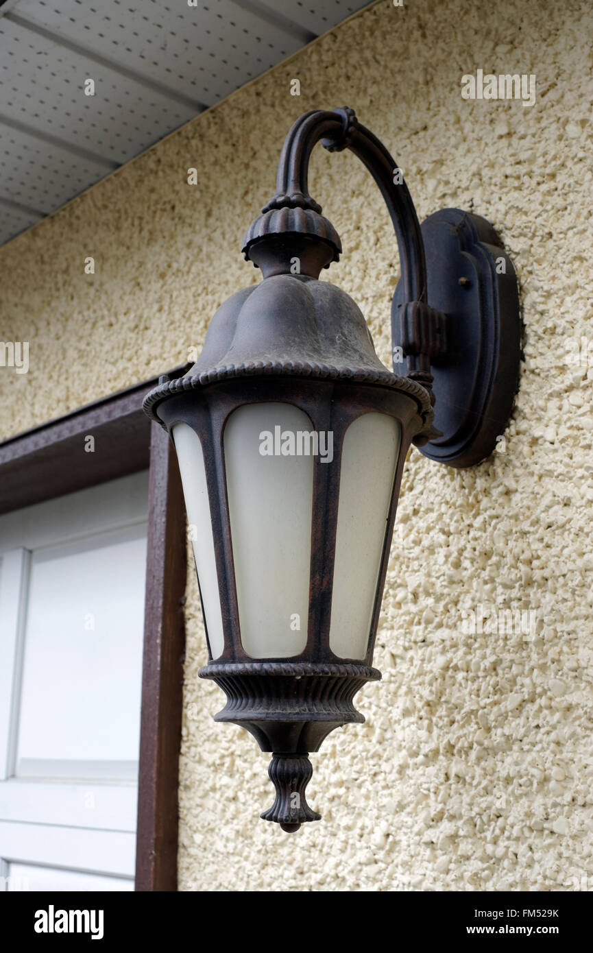 Ornate electric metal lantern on a stucco wall of a house - Stock Image