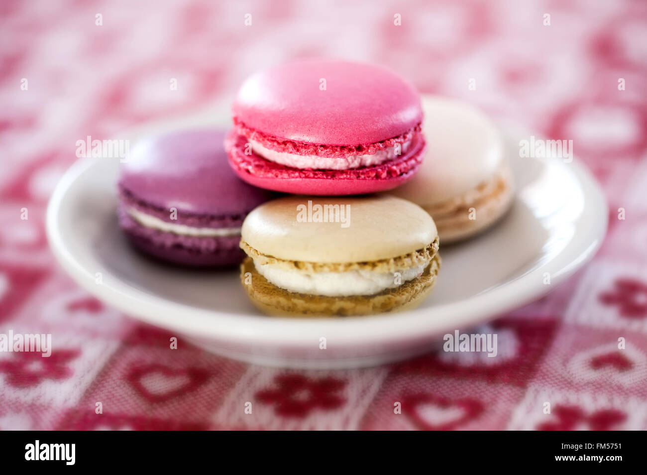 Plate of colorful macaroons made with egg-white, almonds and filled with butter cream - Stock Image