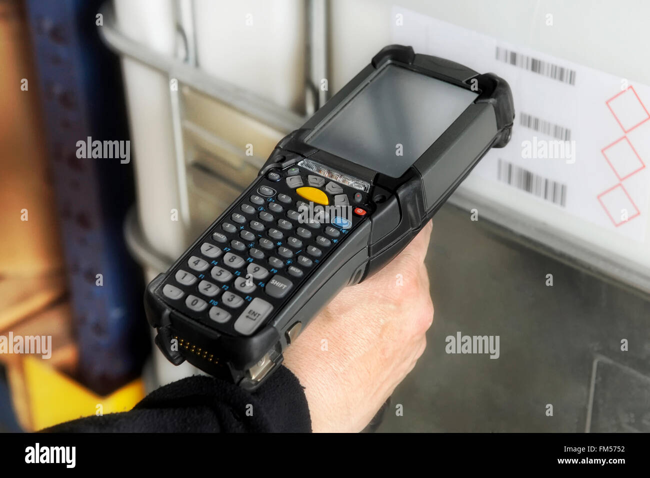 Person scanning a barcode with a handheld electronic scanner - Stock Image