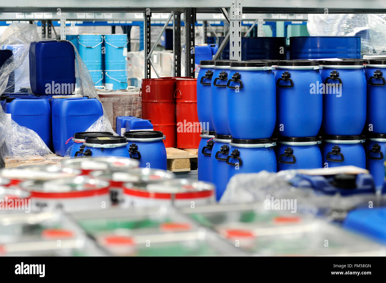 Colorful red metal and blue plastic barrels or drums stored in a warehouse - Stock Image
