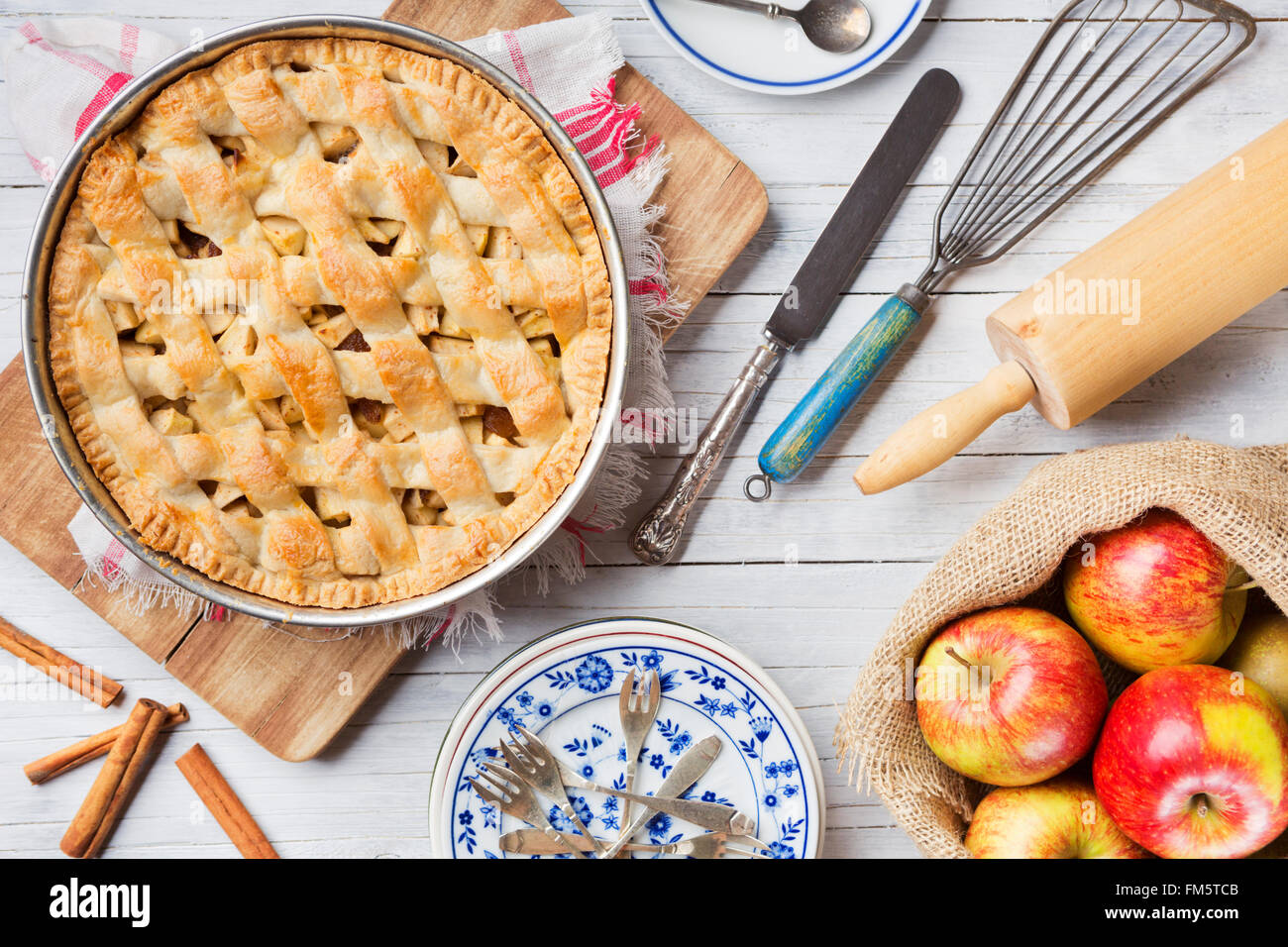 Homemade Dutch apple pie and ingredients on a rustic table. Photographed from directly above. - Stock Image