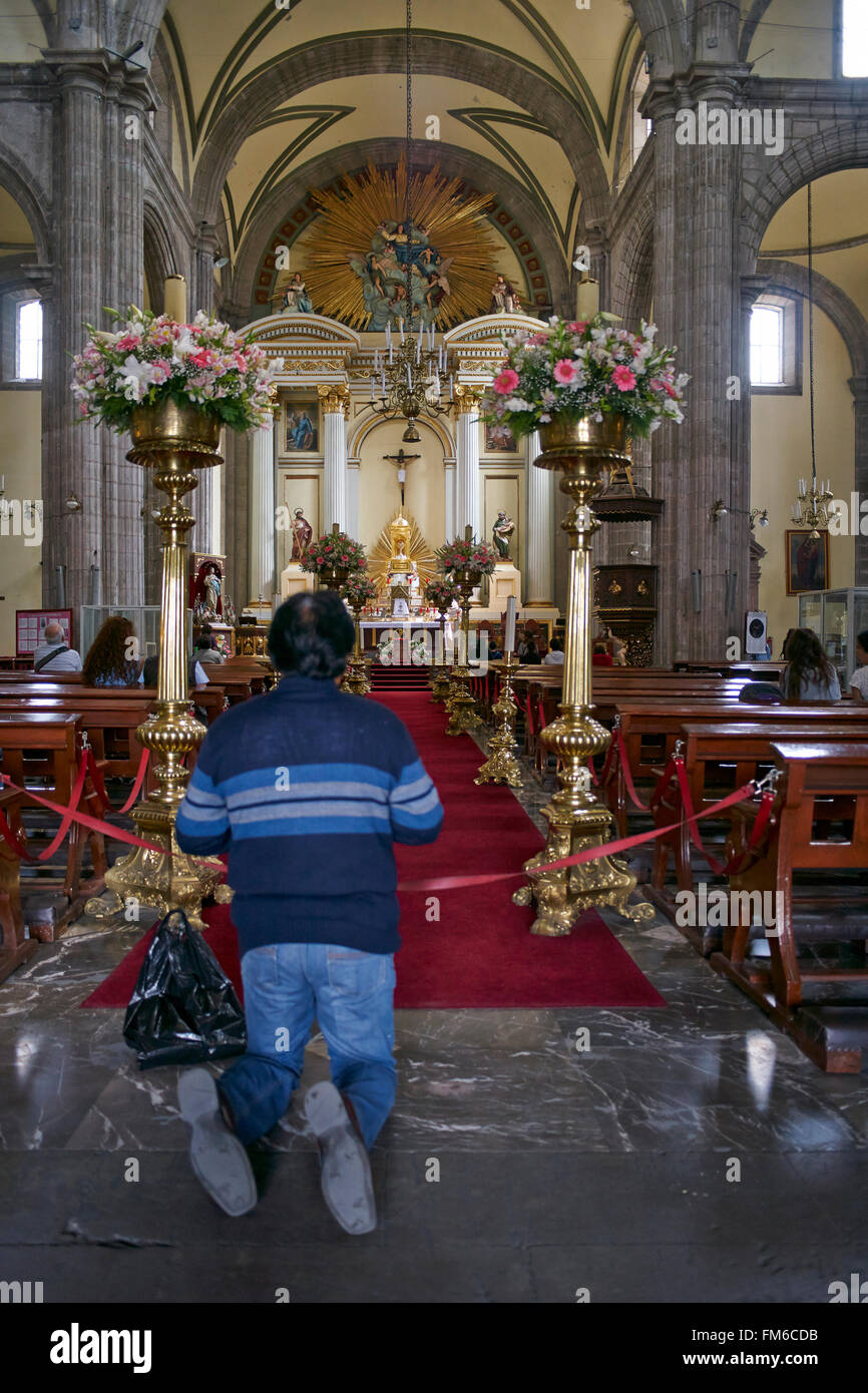 Believer kneeling before an altar in a Mexican church. - Stock Image