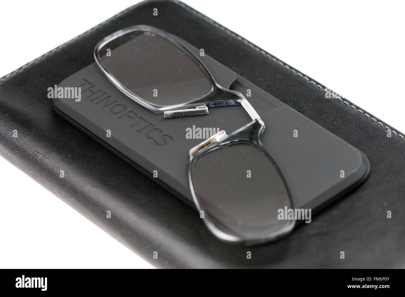 ThinOptics reading glasses on a case stuck to a mobile phone case. - Stock Image