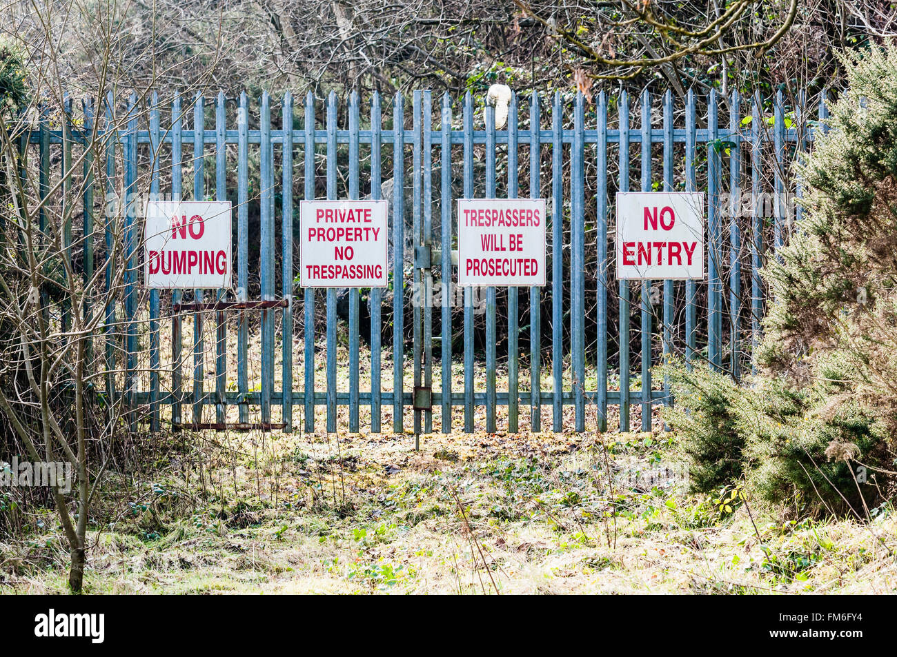 Signs on a security gate warning 'No Dumping', 'Private Property, No Trespassing', 'Trespassers - Stock Image
