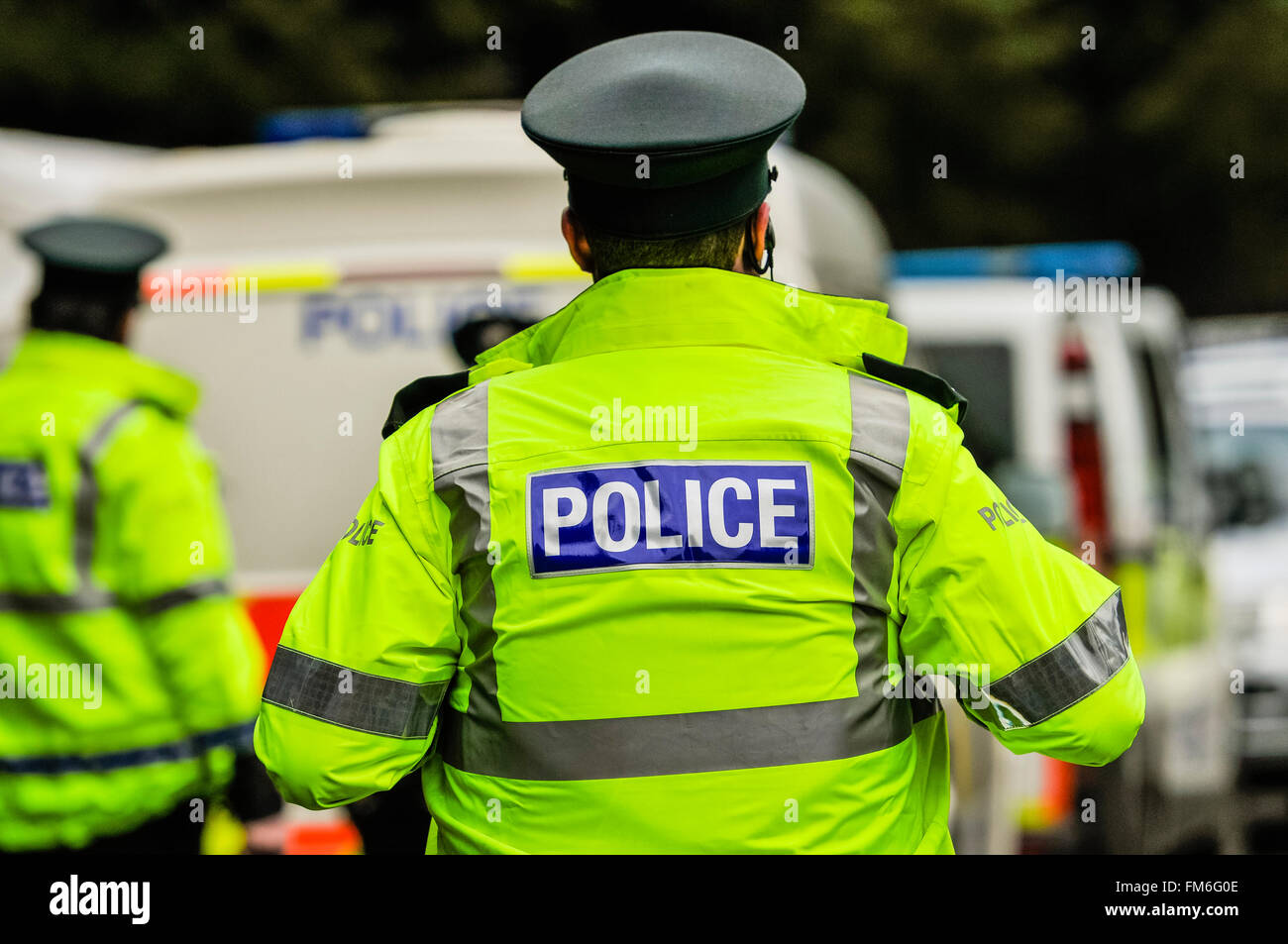 Police wearing high-visibility jackets on duty. - Stock Image