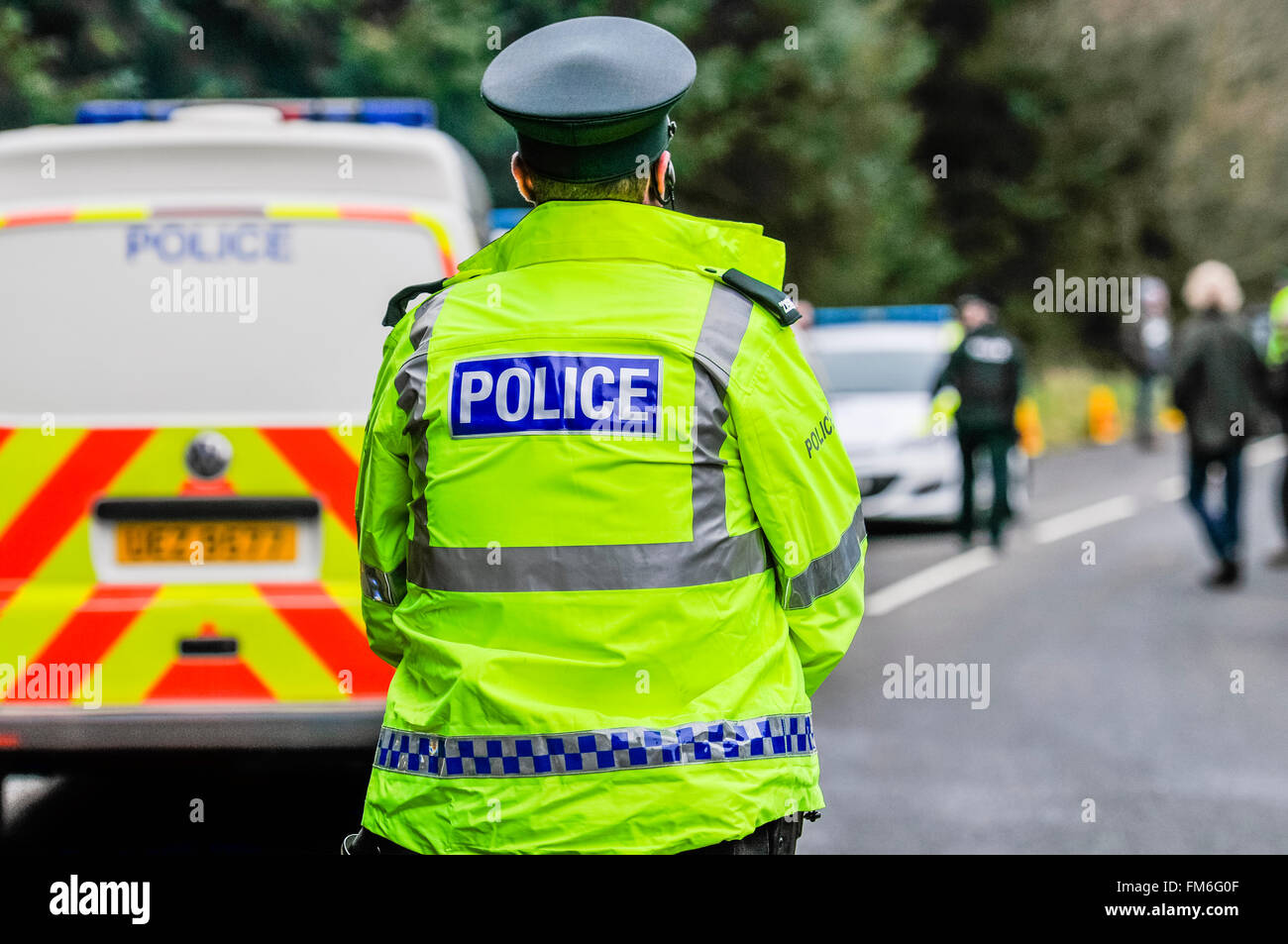 Police wearing high-visibility jackets on duty at a road traffic incident - Stock Image