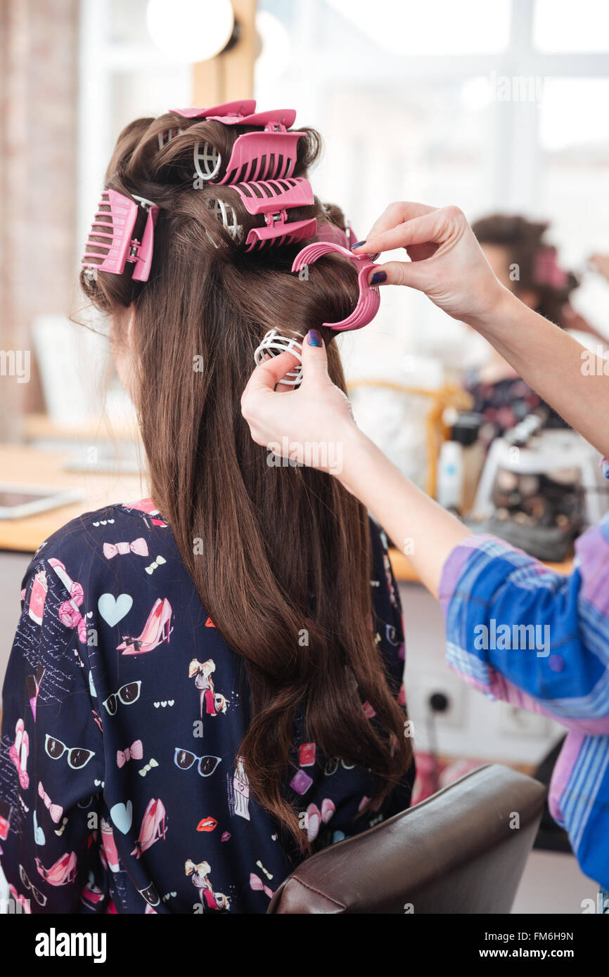 Hairdresser taking off curlers from woman long hair in beauty salon - Stock Image