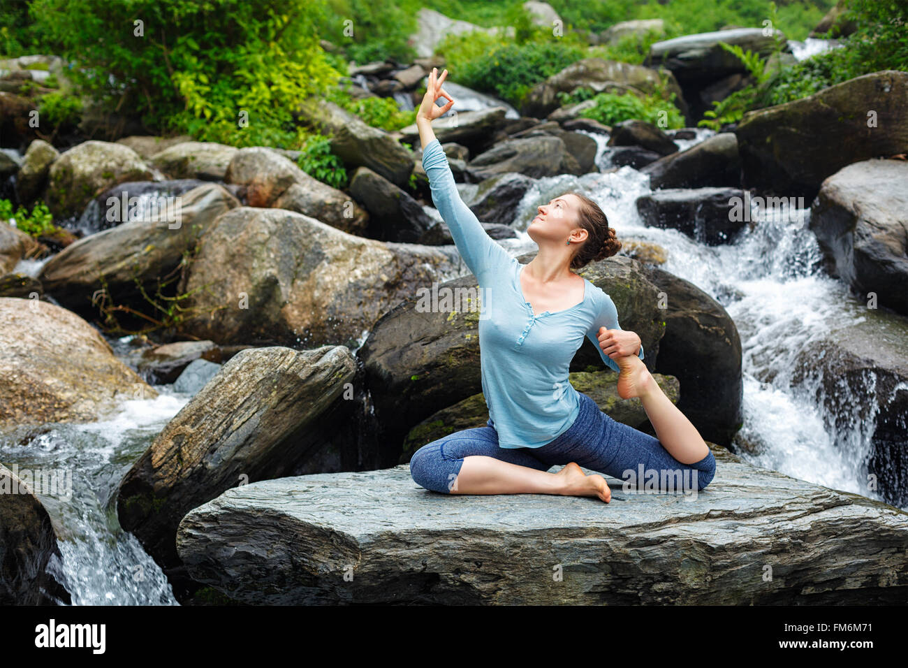 Woman doing yoga outdoors at tropical waterfall - Stock Image