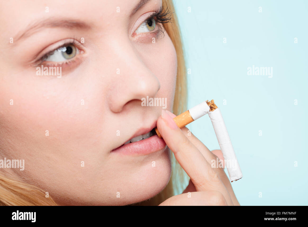 Smiling pretty girl smoking breaked down cigarette. Winning with addicted nicotine problems in young age. Quitting - Stock Image