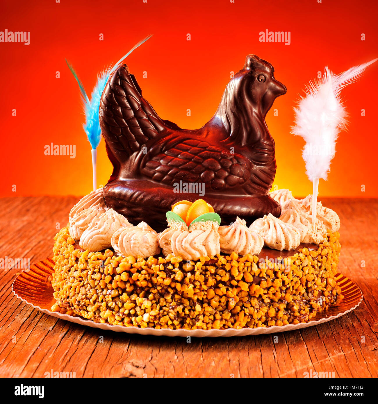 a mona de pascua, a cake eaten in Spain on Easter Monday, ornamented with feathers and a chocolate chicken, on a Stock Photo
