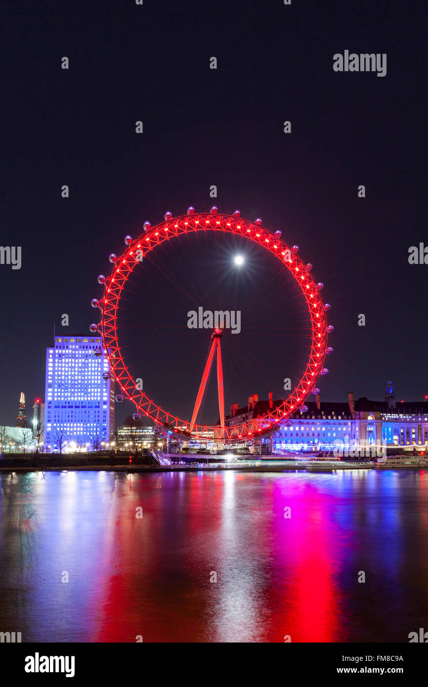 London at night - Illuminated London Eye ferris wheel and city skyline at night, full moon shining behind - Stock Image
