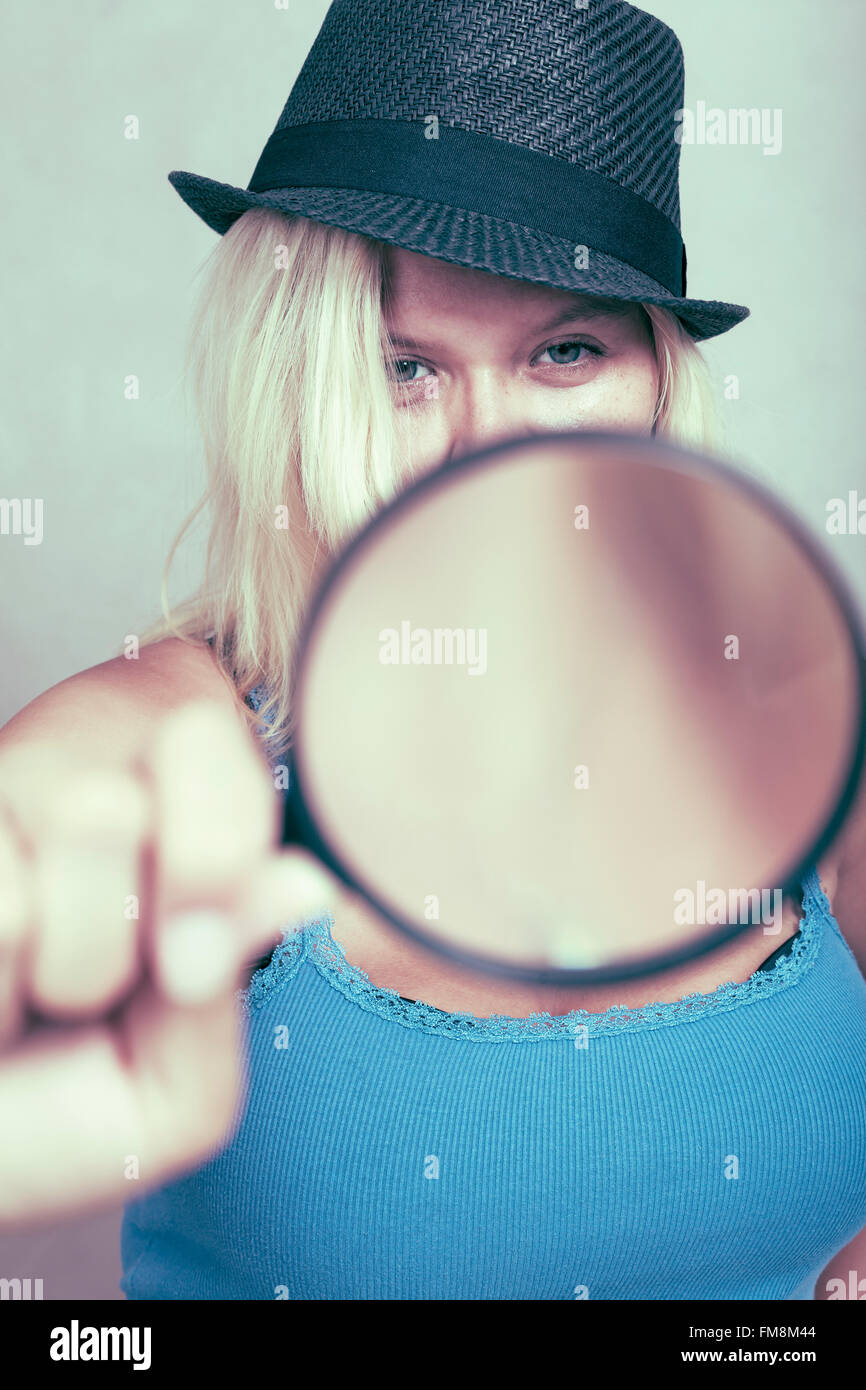 Female detective holding magnifying glass, research and investigation concept. - Stock Image