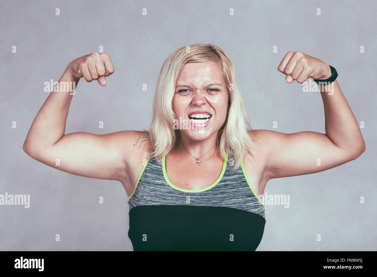 Strong excited muscular woman flexing her muscles. Young blond sporty female showing arms and biceps. - Stock Image