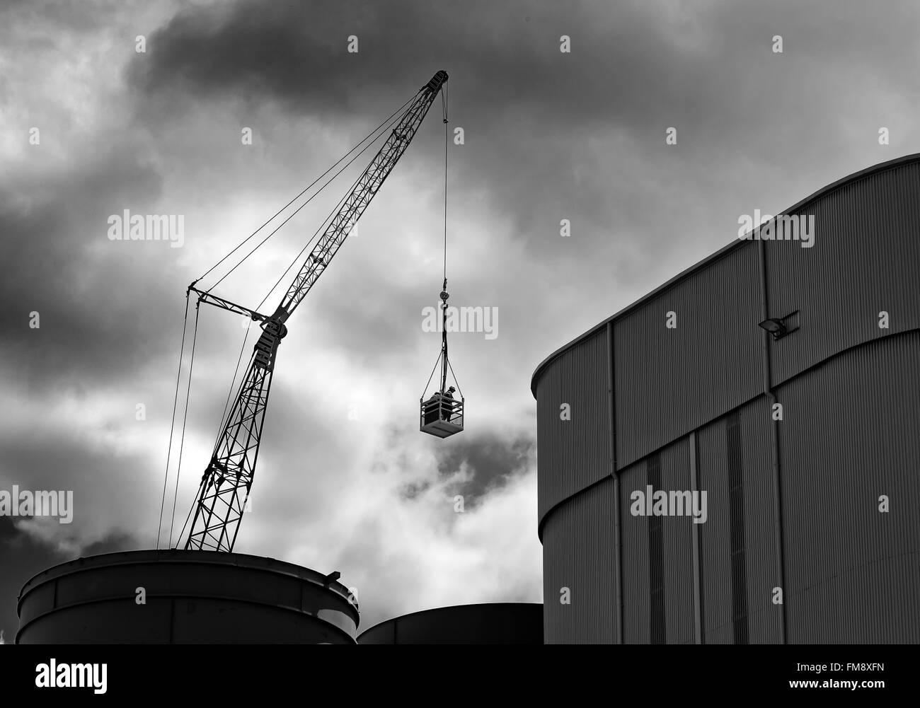 Industrial scene of man in basket under dark sky hoisted by crane onto a silo in brisbane docks - Stock Image