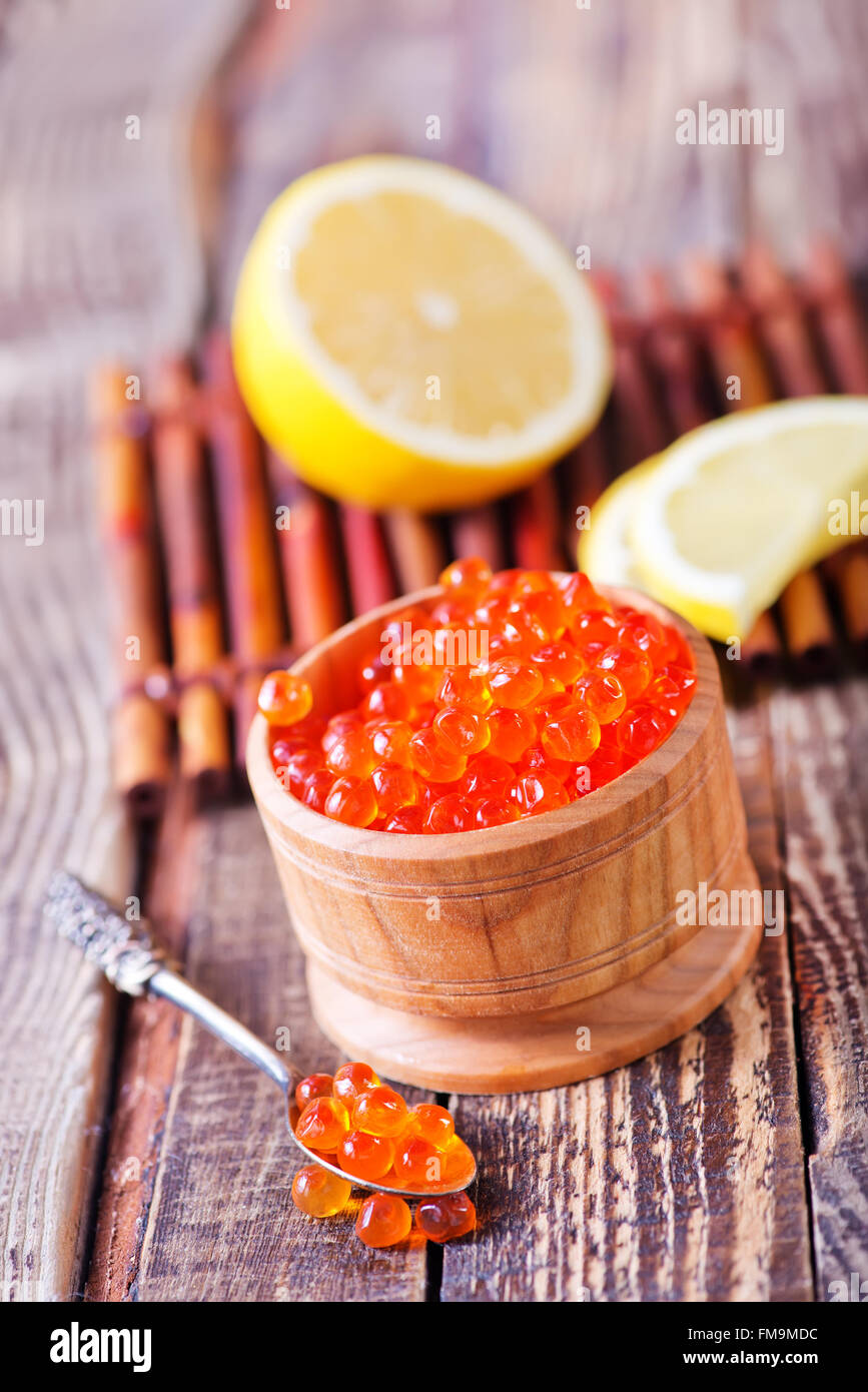red salmon caviar in bowl and on a table - Stock Image
