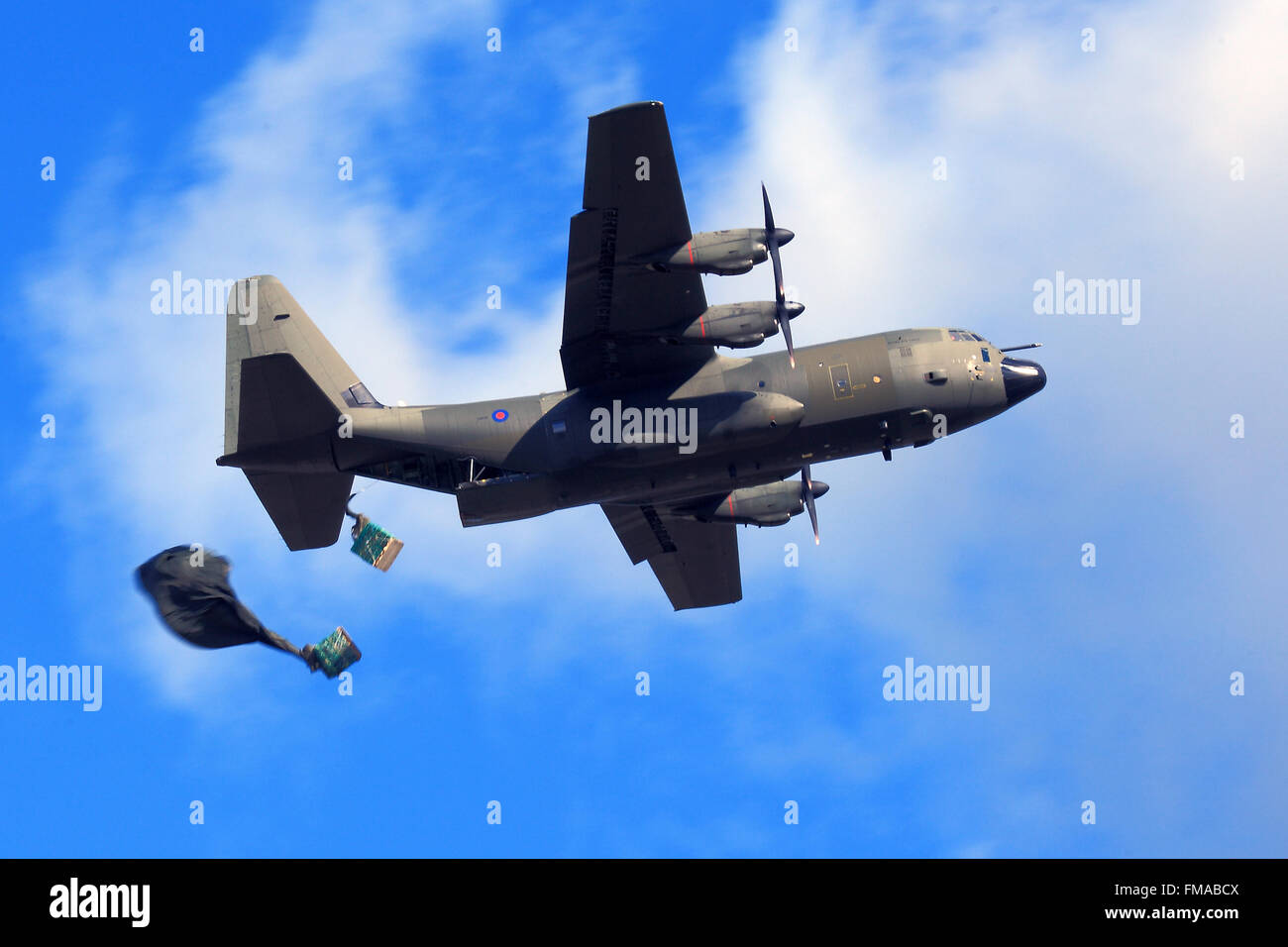 Royal Air Force Hercules transport aircraft carries out a parachute drop of cargo on Salisbury Plain Training Area. - Stock Image