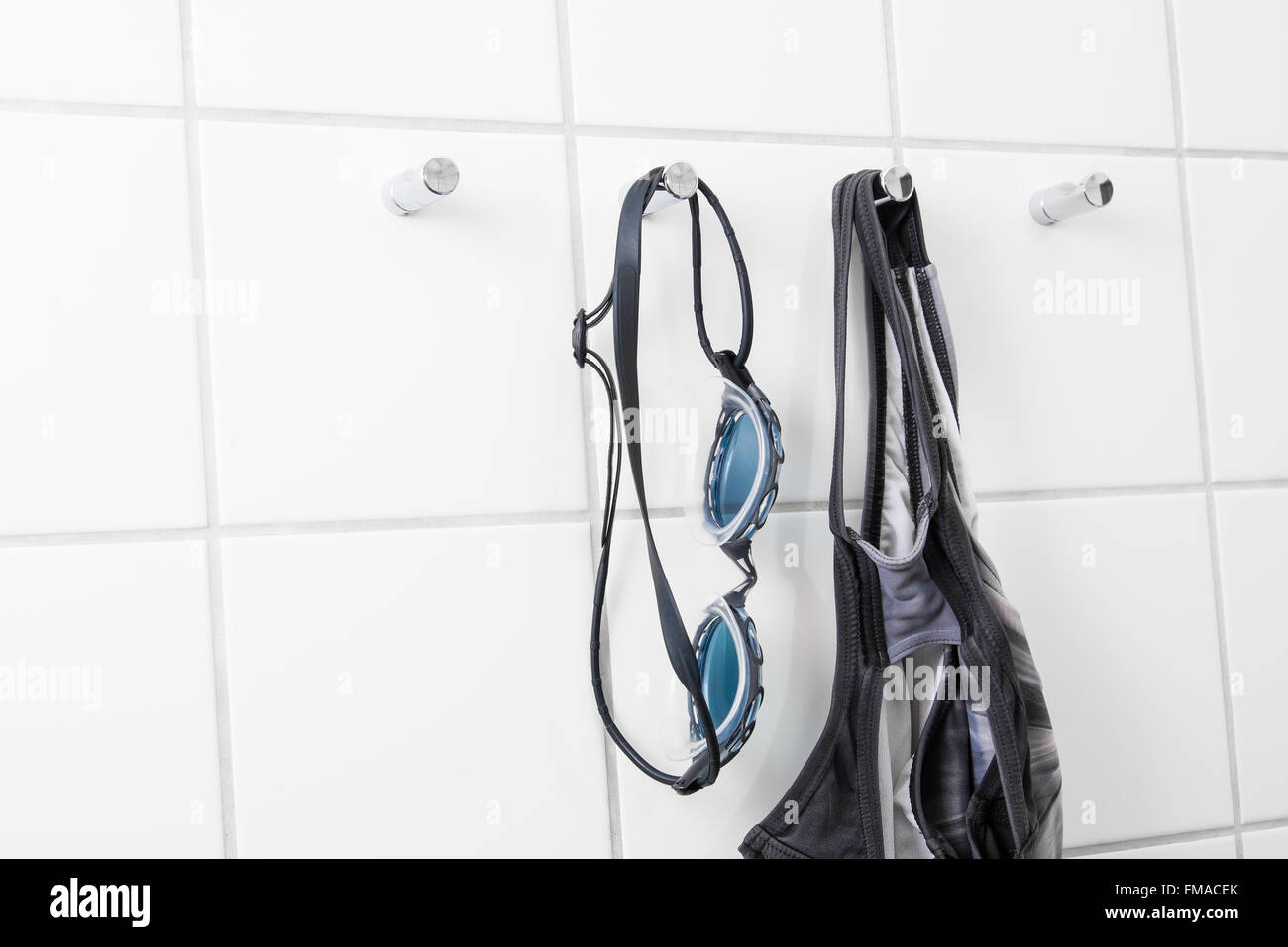 Swimming goggles and bathing suit hanging on tile wall - Stock Image