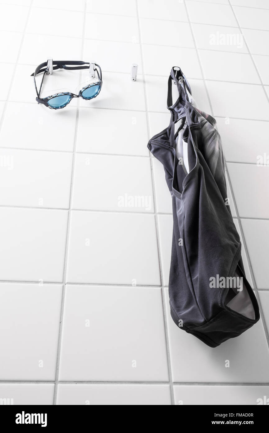 Blue swim goggles and a swimming suit hanging on hooks - Stock Image