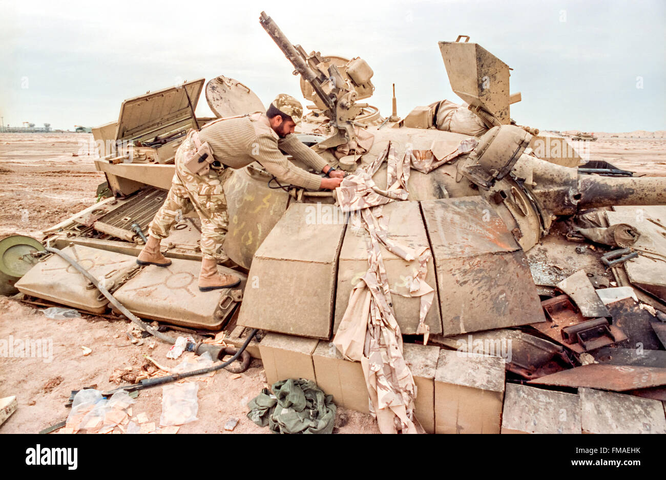 A Qatar soldier examines a destroyed Iraqi T-55 battle tank during clean up operations following the Battle of Khafji - Stock Image