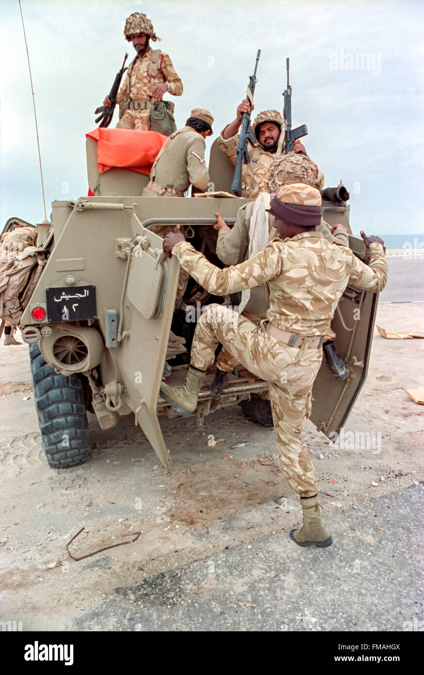 Saudi Arabian soldiers load into an armored personnel carrier during clean up operations following the Battle of - Stock Image