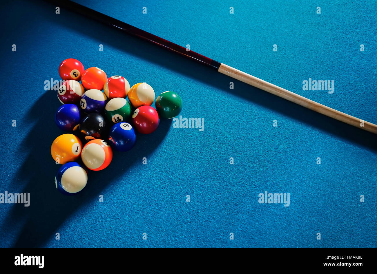 Billiard Balls and Cue on Blue Background - Stock Image