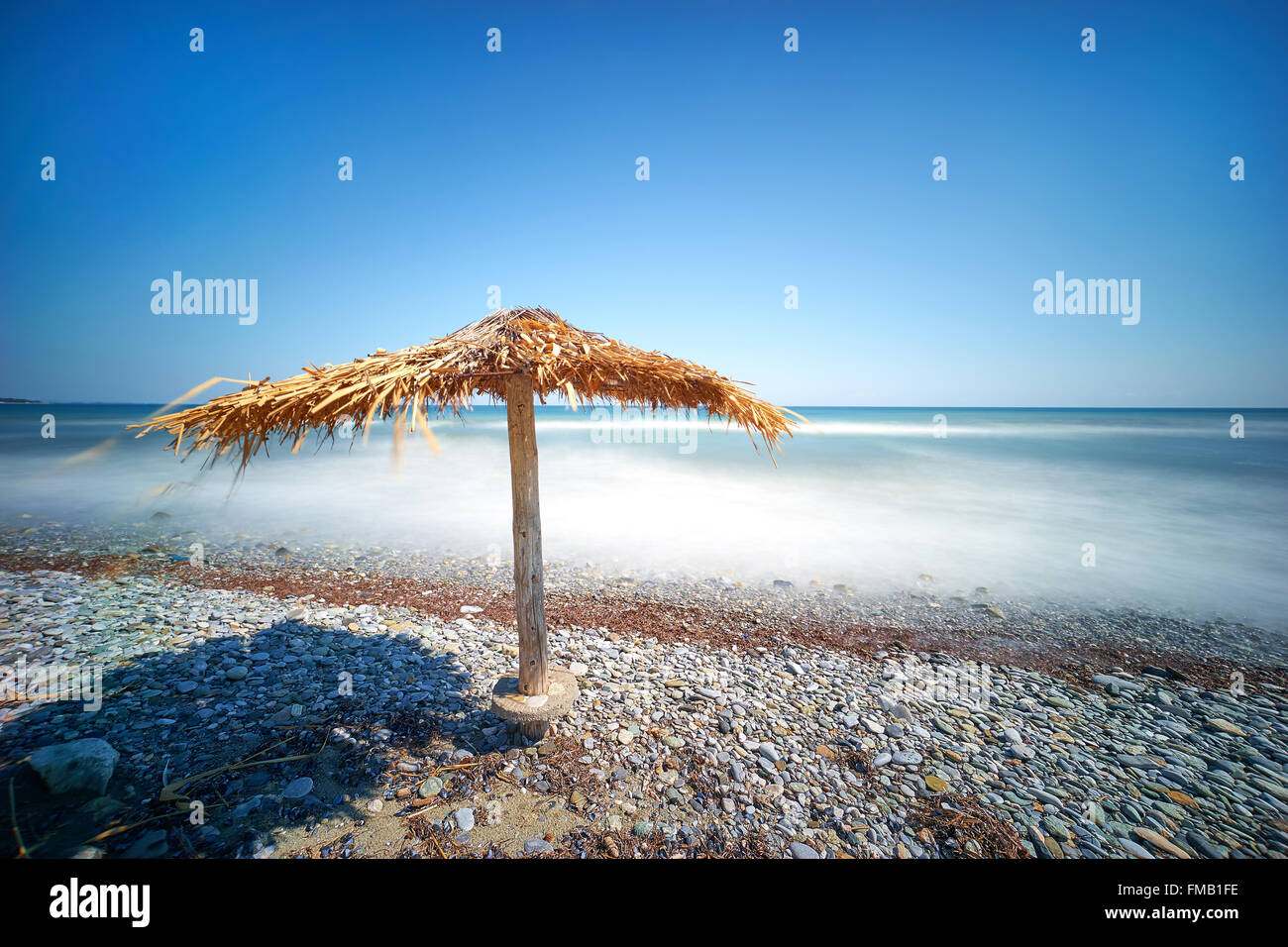Seaside landscape with straw umbrella on the beach. - Stock Image