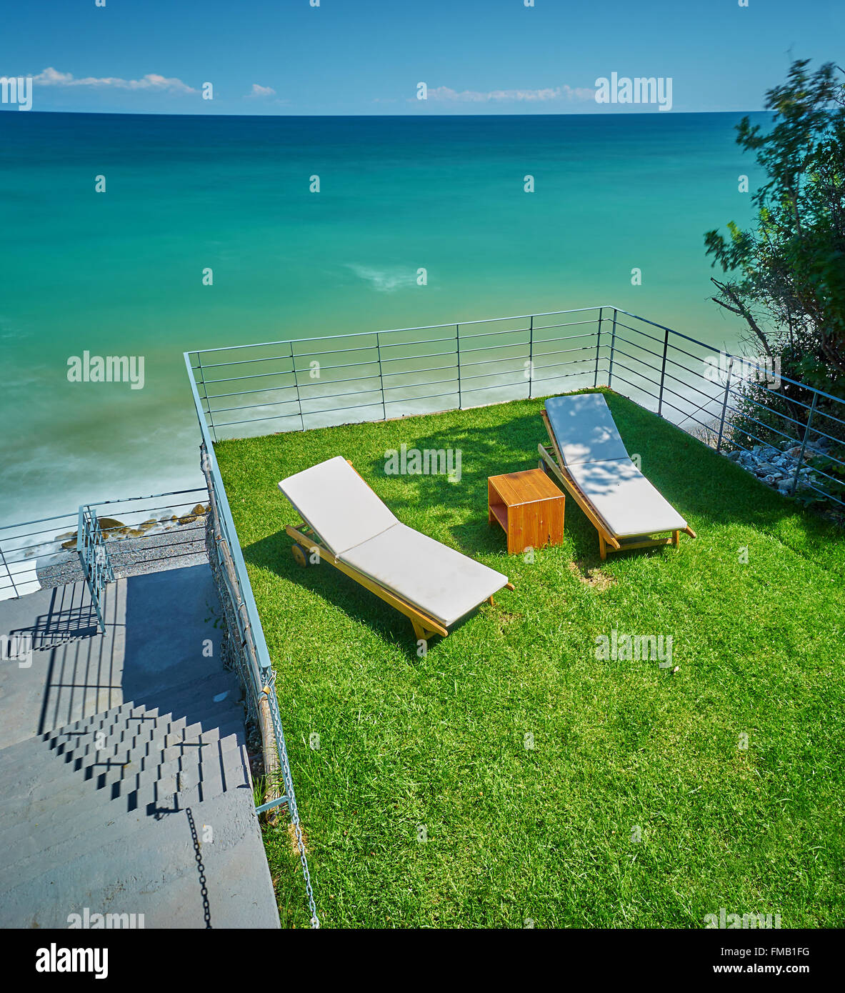 Seaside landscape with sea water, grass terrace and sunbed lounge. - Stock Image