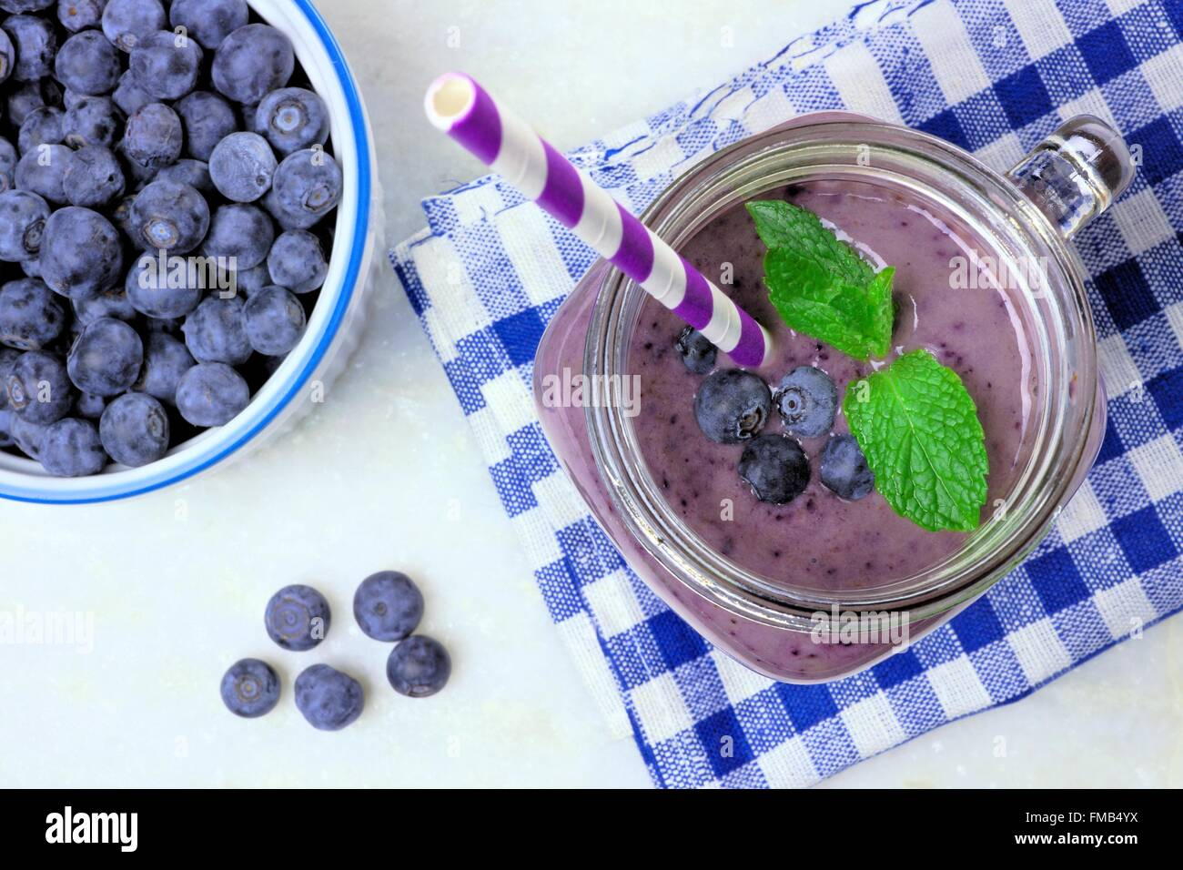 Blueberry smoothie with mint in mason jar mug, downward view on white marble - Stock Image