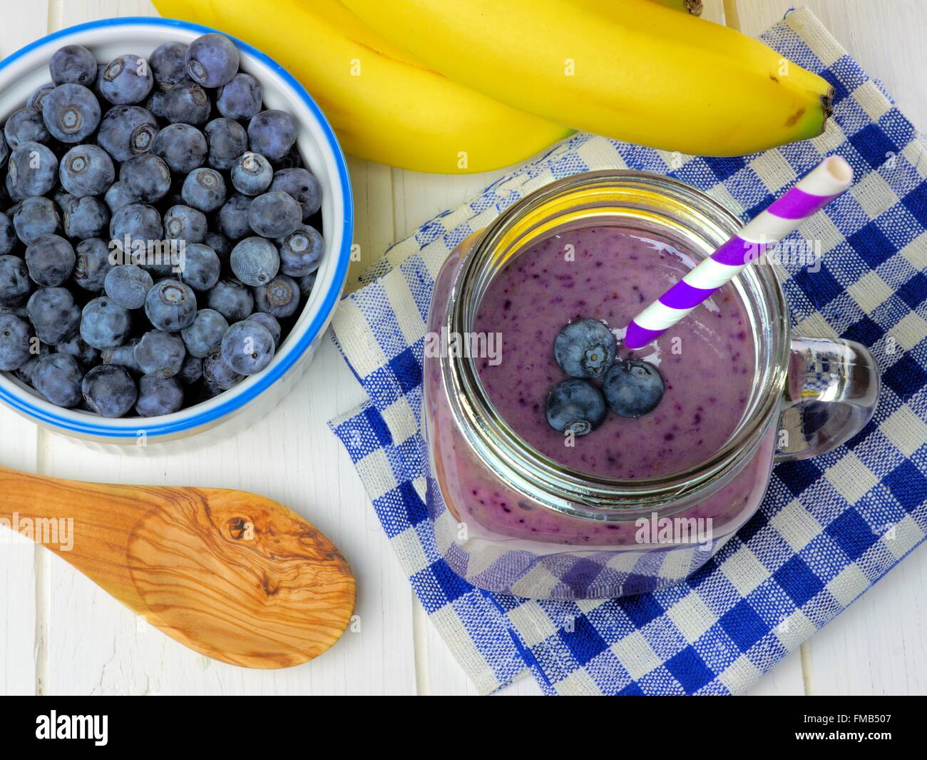 Blueberry smoothie above view with bananas, checkered cloth and spoon on white wood - Stock Image