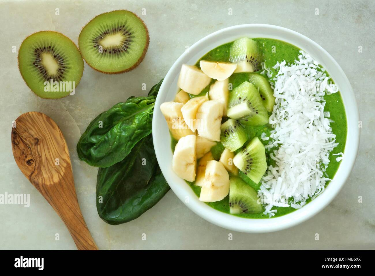 Green smoothie bowl with spinach, bananas, kiwi fruit and coconut with spoon on a white marble background - Stock Image