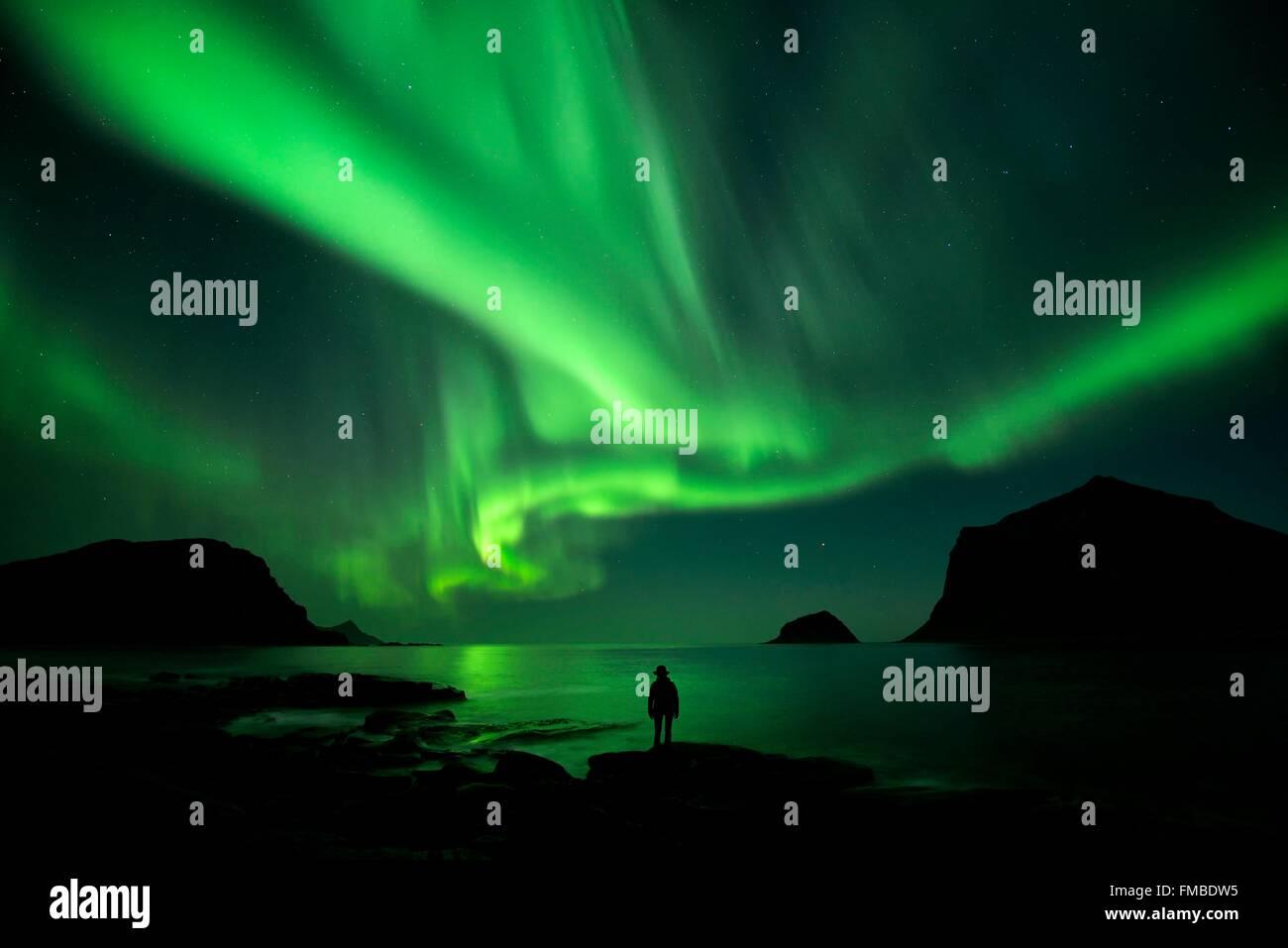 Norway, Nordland, Lofoten islands, Vestvagoy island, Vik beach, silhouette of a woman and northern lights (aurora - Stock Image