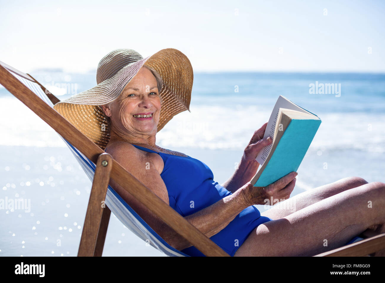 Pretty mature woman reading a book lying on deck chair - Stock Image