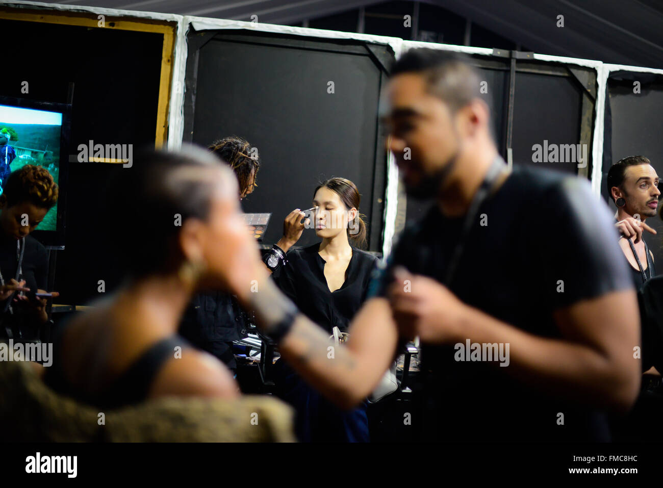 Johannesburg, South Africa. 11th Mar, 2016. Make-up artists prepare models backstage ahead of the presentation of - Stock Image