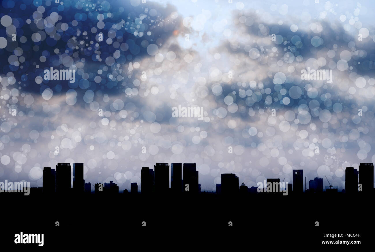 Silhouetted city with light from cloudy sky and light snow blow in the air Stock Photo
