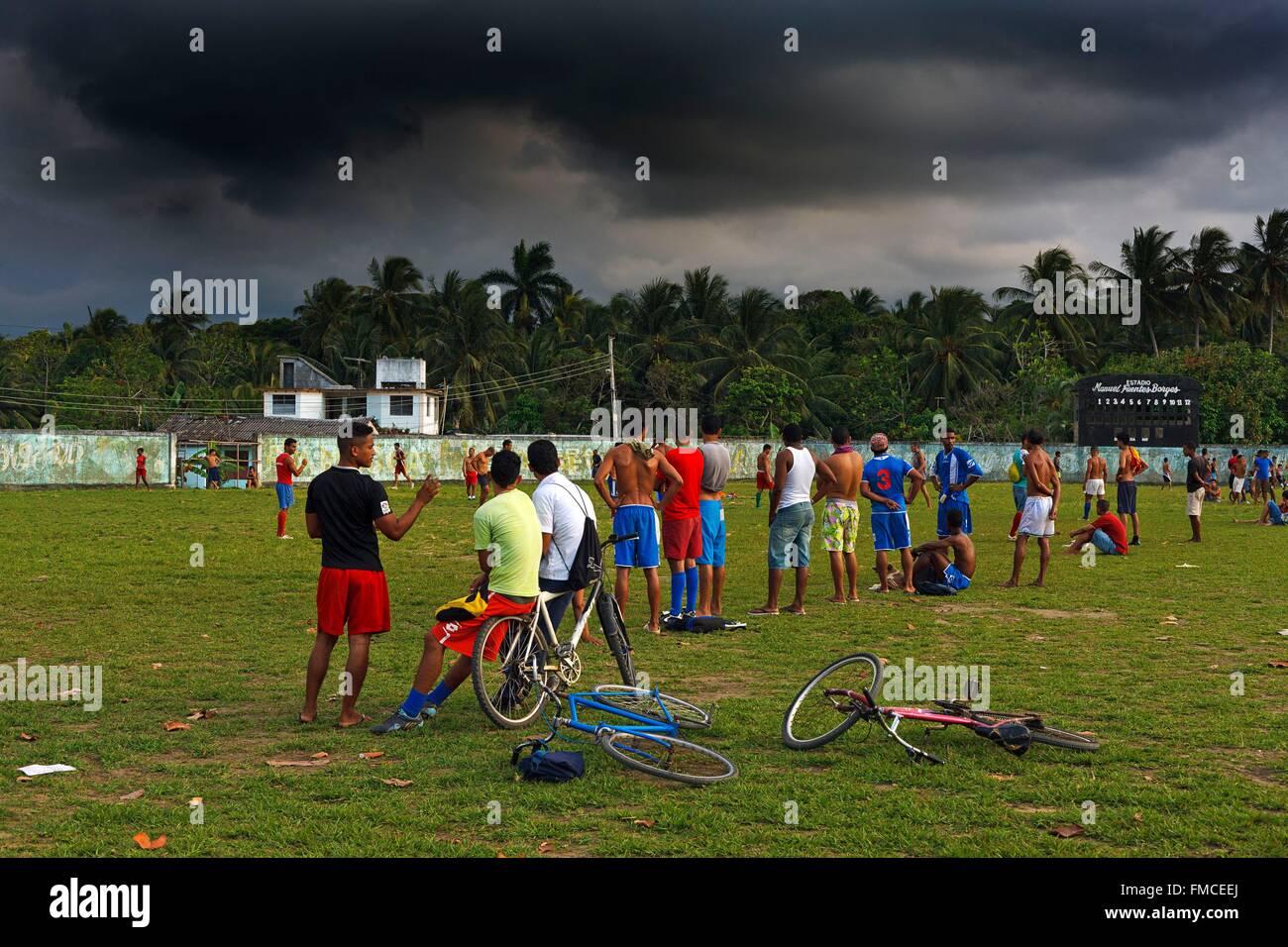 Cuba, Guantanamo, Baracoa, Football players on field under threatening skies - Stock Image