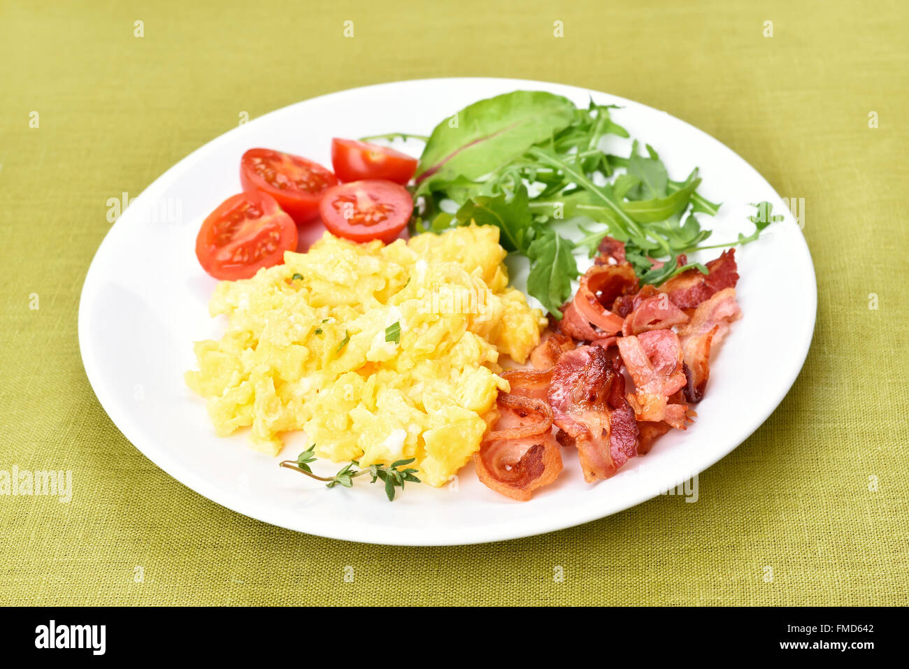 Breakfast scrambled eggs, bacon and vegetable on white plate - Stock Image