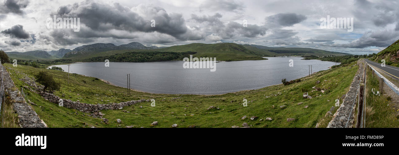 The Poisoned Glen (Dunlewy Lough) lies right at the foot of Errigal. The moody clouds fit the name of the lake. - Stock Image