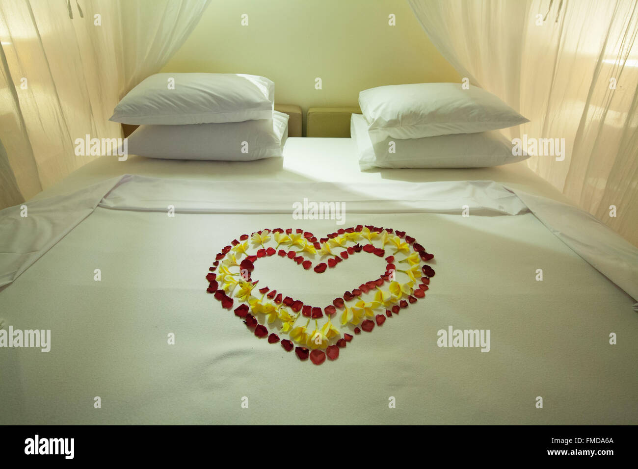 Hotel room with four-poster bed, heart of flowers, decorated double bed, Ubud, Bali, Indonesia - Stock Image