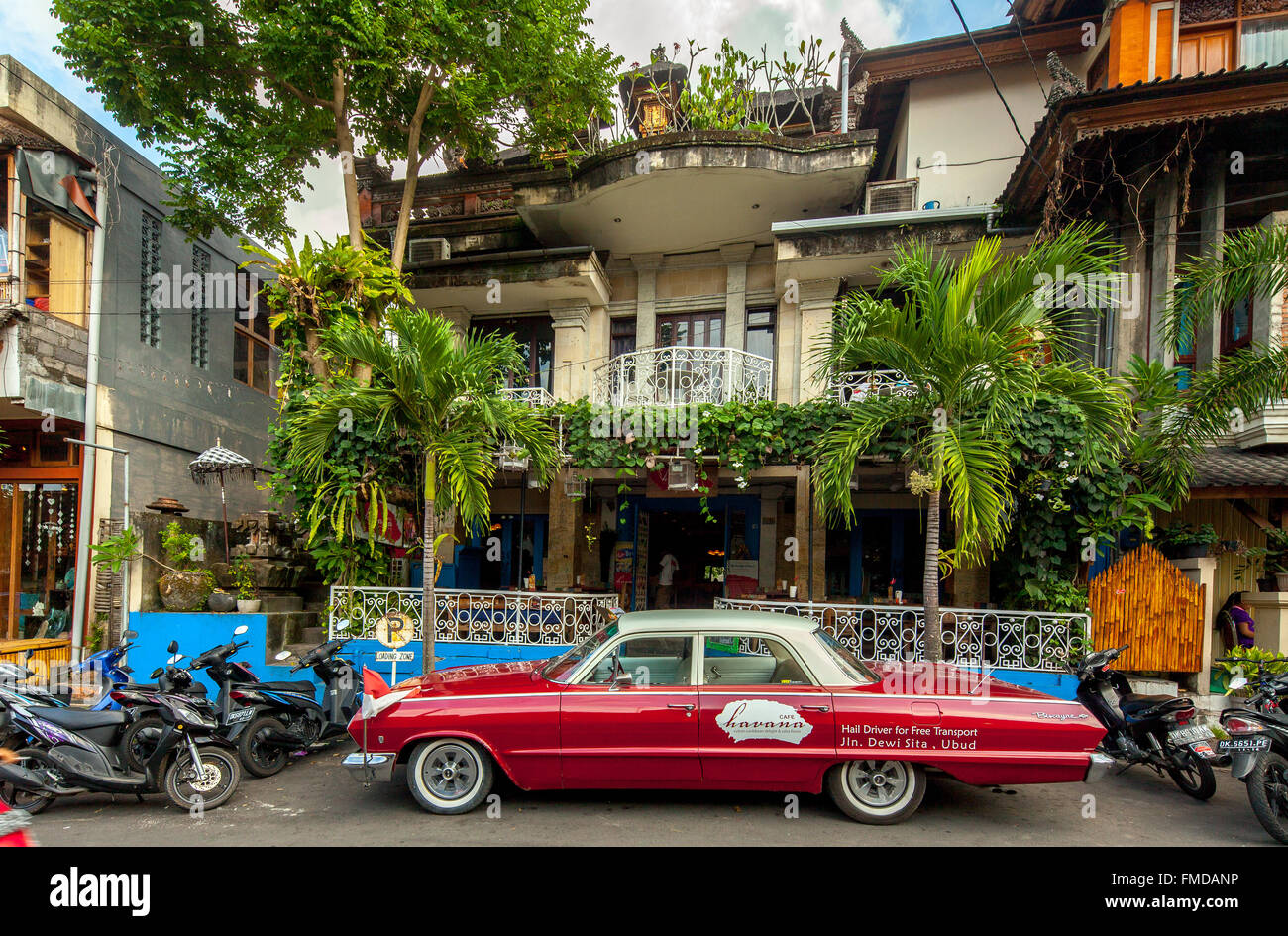Red Chevrolet Biscayne in front of a cafe, street setting, Ubud, Bali, Indonesia - Stock Image