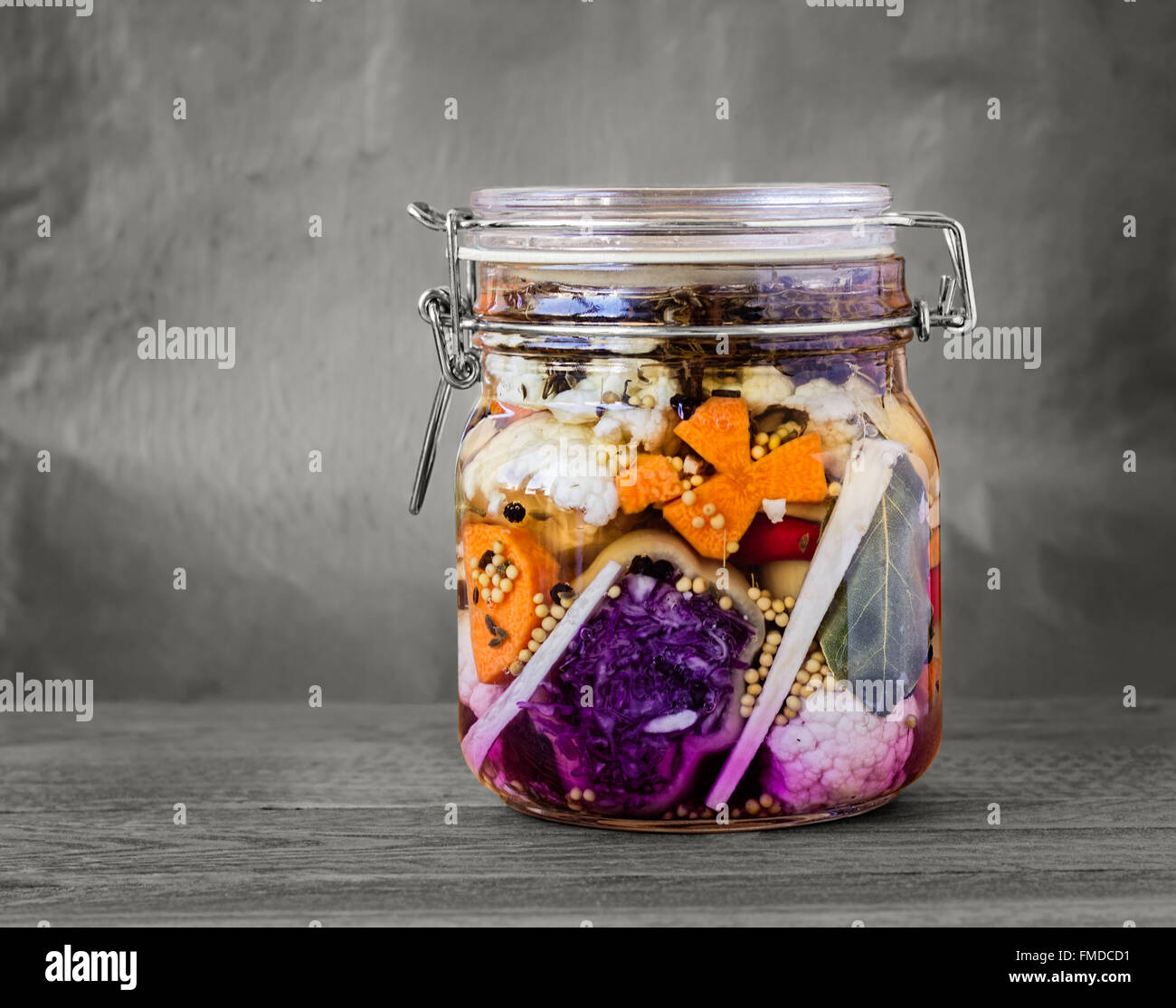 Jar of assorted brined lacto-fermented pickles on a wooden table with desaturated background. - Stock Image